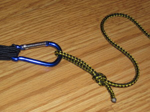 Attach a simple cord to the ring to use for attaching to the hammock and adjusting tension.